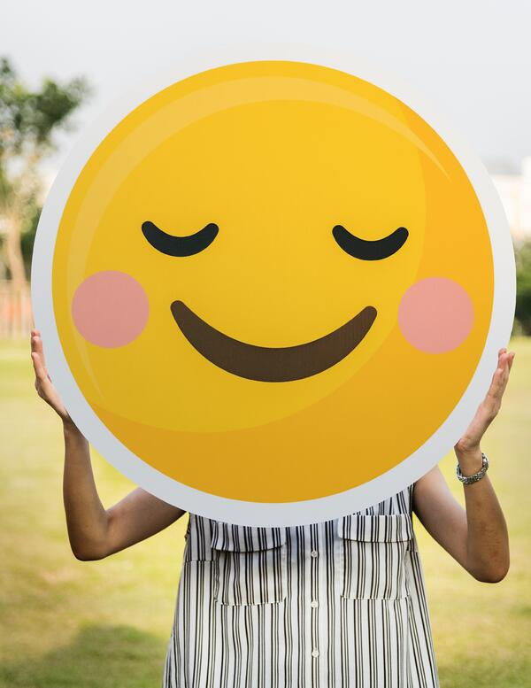 A Person in a Striped Top Holding a Yellow Smiling Face Emoji in Front of their Face