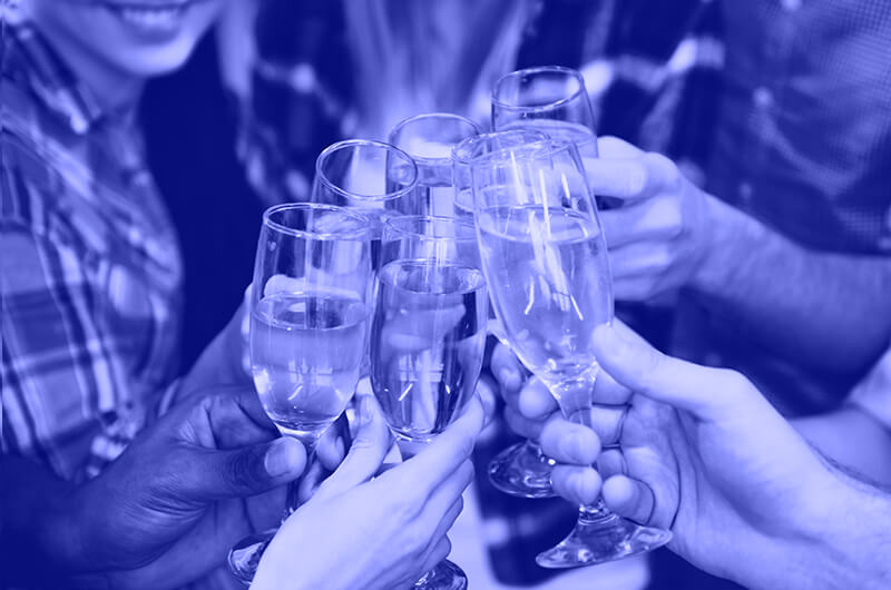 Blue Image of Seven People Tapping Prosecco Glasses